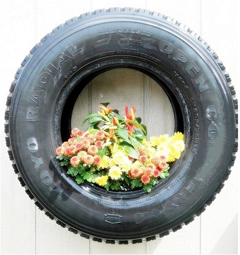 An unpainted black tyre with orange, white and yellow flowers. Look how they pop against the black tyre. Image source: http://www.curbly.com/users/mollymc/posts/13691-roundup-7-creative-upcycled-planter-ideas